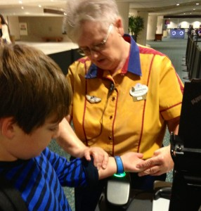 A Cast Member shows my son how to use his MagicBand at our first spot -- Disney's Magical Express